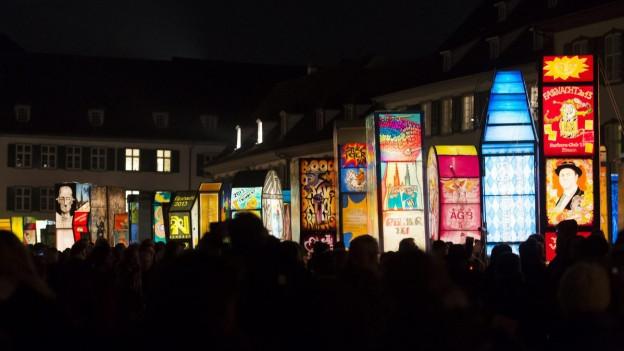 Laternenaustellung auf dem Basler Münsterplatz bei Nacht. Viele Menschen tummeln sich zwischen den beleuchtetetn Laternen.