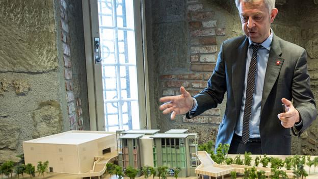 Ein Mann steht vor einem Architekturmodell
