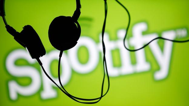 Kopfhörer hängen vor einem Spotify-Logo