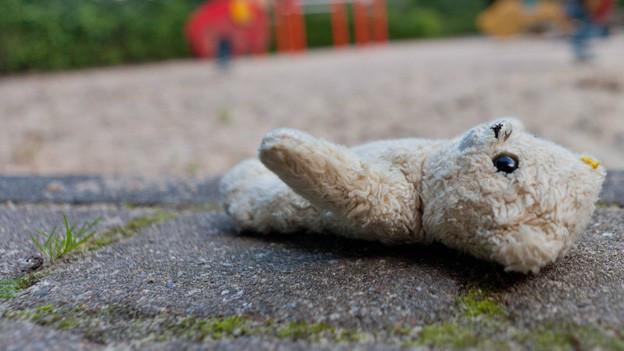 Teddybär liegt einsam neben verlassenem Kinderspielplatz.