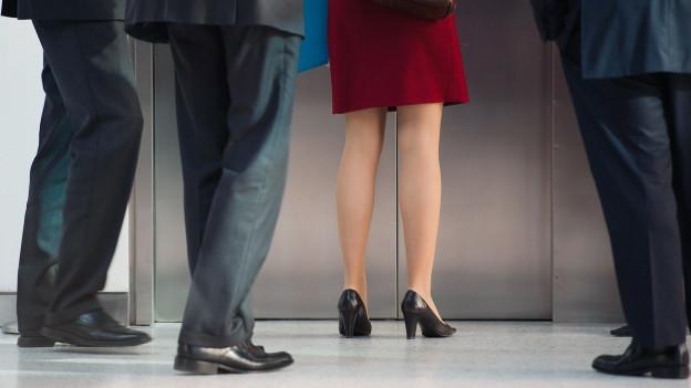 Eine Frau und ein paar Männer stehen in einem Korridor und warten auf den Lift.