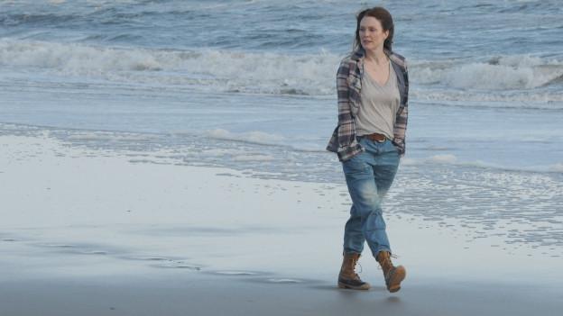 Eine Frau spaziert am Strand.