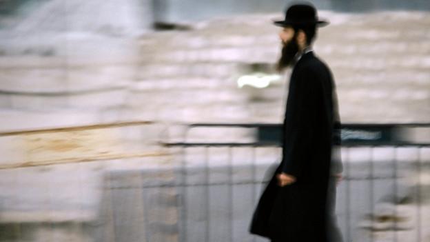 Ein jüdisch gekleideter Mann geht eine Strasse lang.