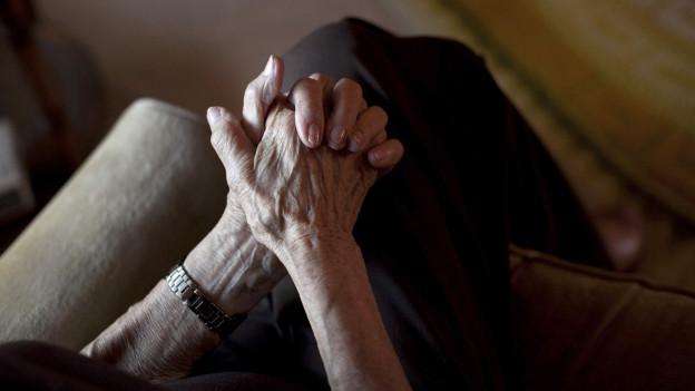 Eine Hand einer älteren Frau auf einer Schoss.