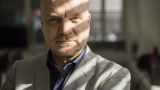 Porträt von Hansi Voigt mit Schein vom Rolladen im Gesicht.