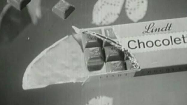 Eine Werbung von Chocoletti. Man sieht eine Tafel und Schokostückchen.