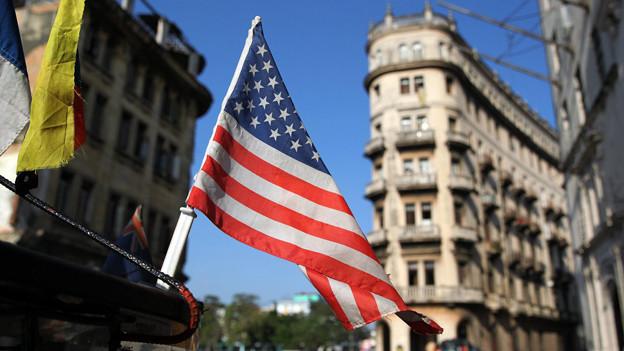 Ein kleine US-Flagge aus Plastik vor historischen Gebäuden