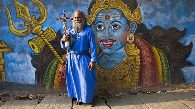 Ein indisch aussehender Mann in blauem Gewand steht mit einem Kruzifix in der Hand vor einer Wand, auf die eine grosse indische Gottheit gemalt ist.