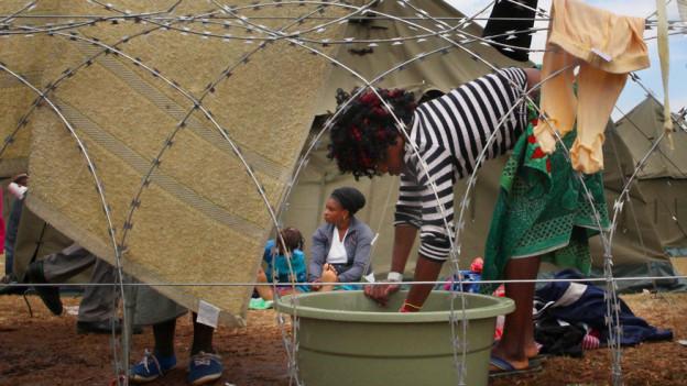 Drauen in einem Flüchtlingslager, geschützt durch Stacheldraht.
