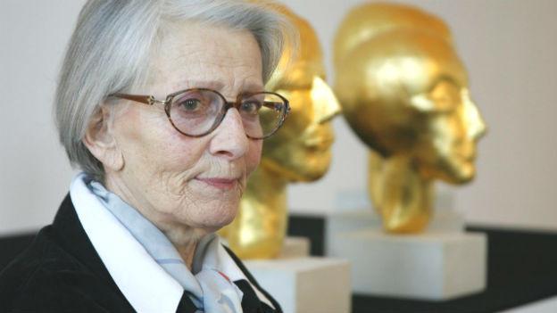 Eva Aeppli vor goldenen Skulpturen. Sie trägt eine Brille.