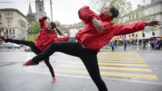Zwei Frauen tanzen auf der Strasse.