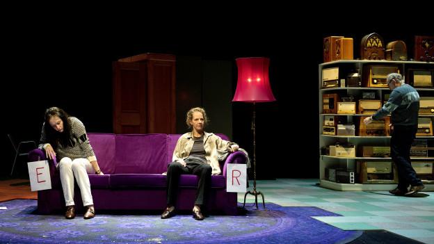 Frau und Mann sitzen auf Sofa, ein weiterer Mann steht vor Regal.