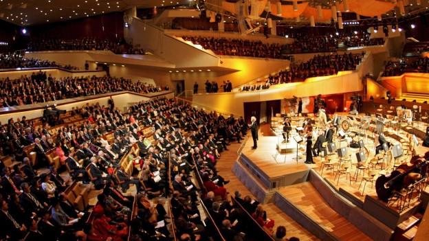 Konzertsaal der Berliner Philharmonie mit Sir Simon Rattle auf der Bühne.