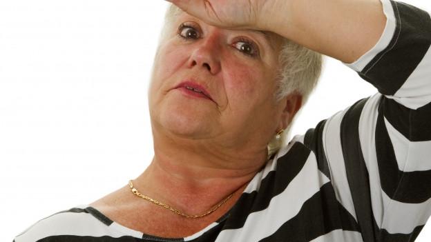Eine Frau mittleren Alters hält ihre Hand an die Stirn und wirkt erschöpft.