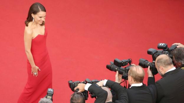 Natalie Portman auf dem roten Teppich, vor ihr Fotografen.