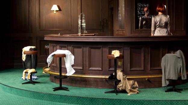 Bar in dunklem Holz, grüner Teppich, Frau steht mit Gesicht zur Wand hinter der Bar.