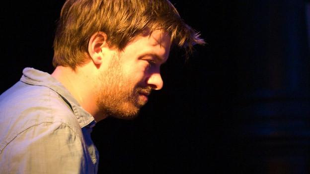 Colin Vallon spielt Klavier im Scheinwerferlicht.