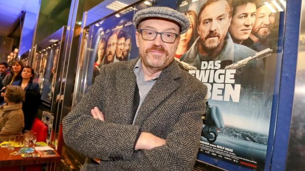 Josef Hader vor dem Kinoplakat «Das ewige Leben».