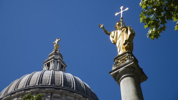 Eine Statue mit Kruzifix vor einem Dom.