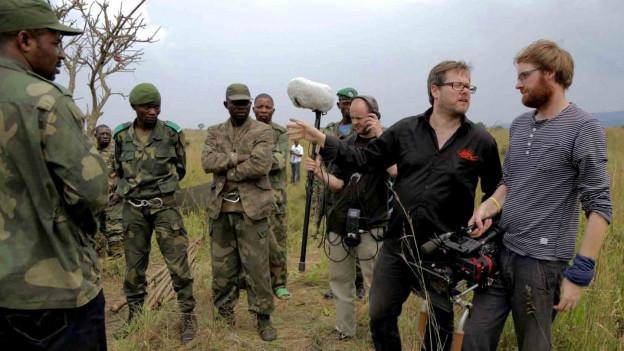 Kamerateam und Männer in Carmouflage-Kleidung.
