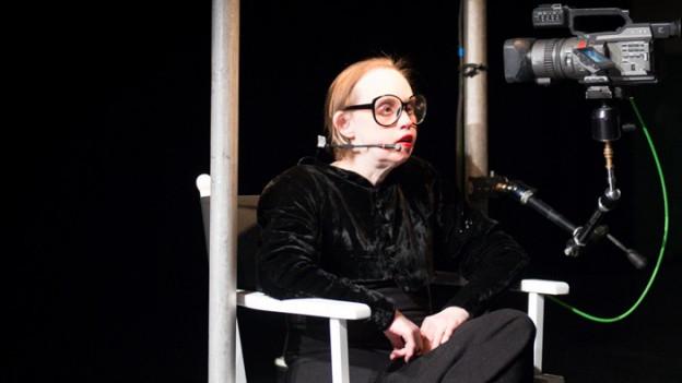Frau in einem Regiestuhl mit einer Kamera, die sie filmt.
