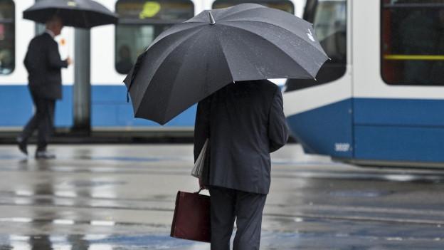 Am Zürcher Paradeplatz wartet ein Bankangestellter auf das Tram