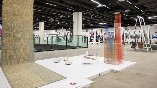 Schalen und andere Objekte sind in einer Halle ausgestellt.