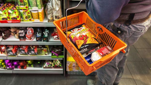 Ein Mann kauft in einem Lebensmittelladen ein. Er hält einen orangen Korb.