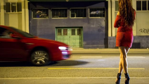 Eine Sexarbeiterin steht an der Strasse.