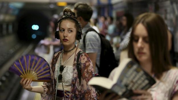 Ein Mädchen mit Fächer in der Londoner U-Bahn.