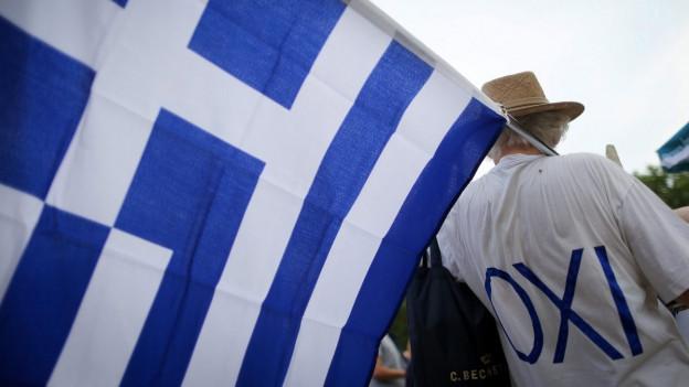 Ein Mann protestiert mit einem «Nein»-Shirt und griechischer Flagge während einer Demonstration in Berlin.