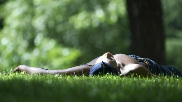 Ein junger Mann in Madrid macht Siesta im Park.