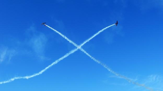 Blauer Himmel, auf dem sich die Kondensstreifen zweier Flugzeuge kreuzen.