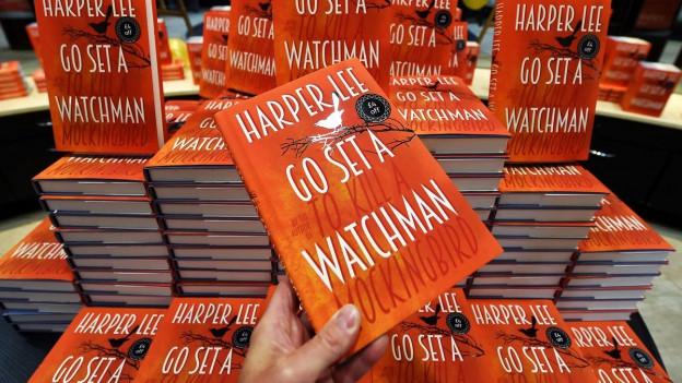 Das neue Buch von Harer Lee (oranges Cover) liegt aufgestapelt in einem Buchladen.