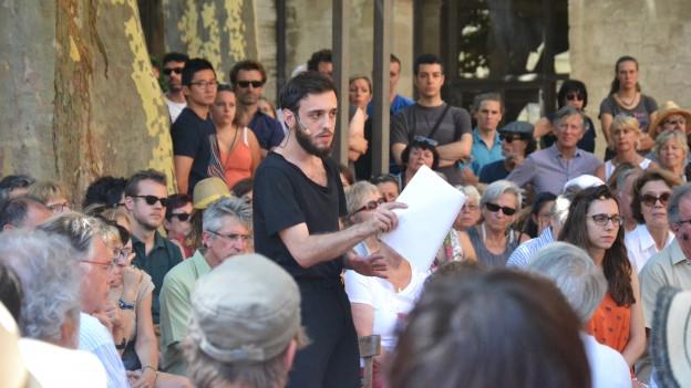 Ein Mann spricht im Freien inmitten einer Gruppe Menschen.
