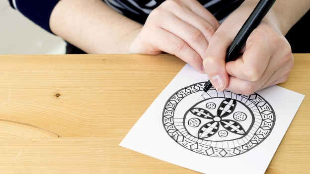 Eien Frau zeichnet Mandala.