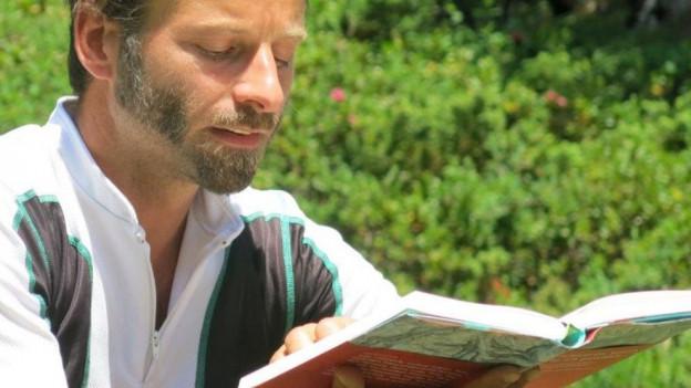 Urs Mannhart liest aus einem Buch vor.