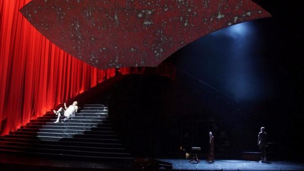 Auf einer Bühne ist eine grosse Treppe zu sehen, auf der sich eine helle beleuchtete Gestalt befindet.