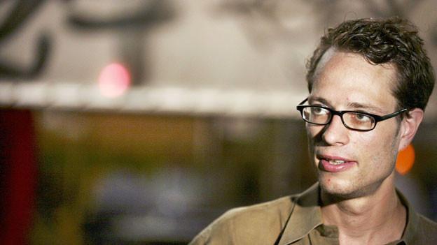 Stefan Kaegi hat kurzes braunes Haar und trägt eine Brille.