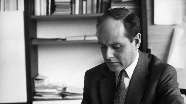 Schwarz-Weiss-Porträt von Löffler bei der Arbeit im Büro.