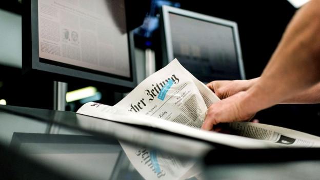 Ein Mitarbeiter der Druckerei blättert in einer frisch gedruckten NZZ-Ausgabe.