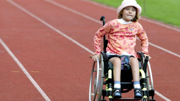 Ein Mädchen im Rollstuhl rollt über eine Laufbahn.