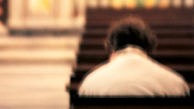 Verschwommene Gestalt sitzt in einer leeren Kirche.