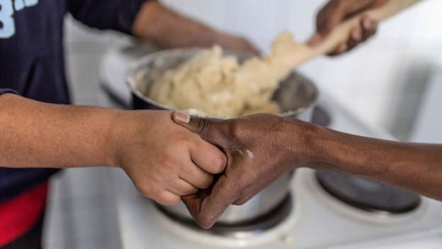 Verschränkte Hände: Flüchtlinge in der Küche eines Asylzentrums.