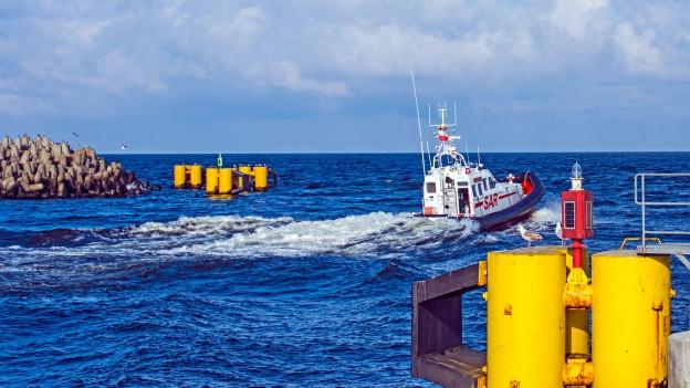 Ein Boot der Küstenwache fährt in Richtung offenes Meer.