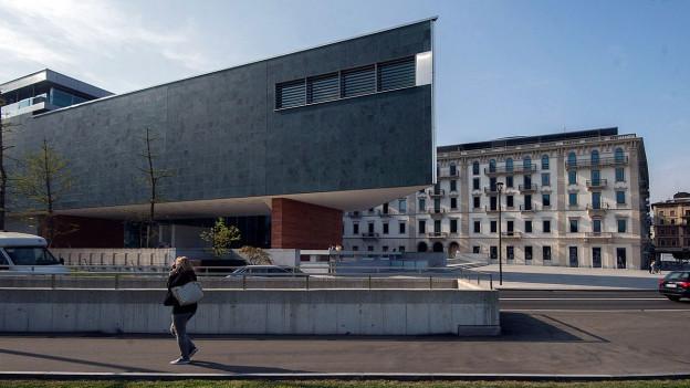 Ein modernes Gebäude im Vordergrund. Dahinter die Fensterfassade eines alten Hotels.