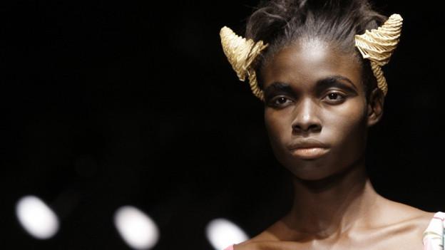 Frau auf dem Laufsteg mit goldenen Hörnchen im Haar.
