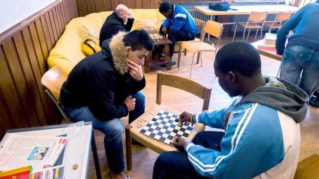 Zwei Männer spielen Schach. Das Schachbrett liegt auf einem Stuh. Dahinter spielen zwei weitere Männer Schach.