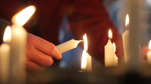 Eine Hand zündet eine Kerze an.