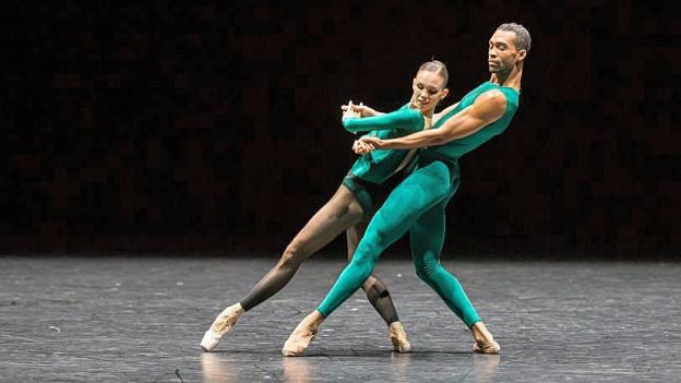 Eine Tänzerin und ein Tänzer in grünen, enganliegenden Kostümen.